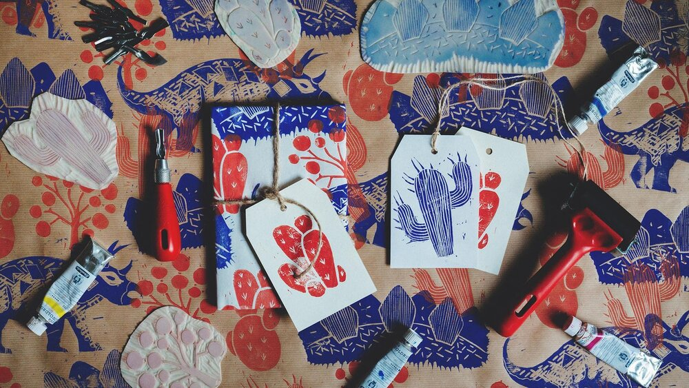 Pictured: Dinosaur Linocut Wrapping Paper & Gift Tags by Evgeniya & Dominic Righini-Brand from their Skillshare course,    Printmaking at Home: Creating Linocut Wrapping Paper & Gift Tags   .