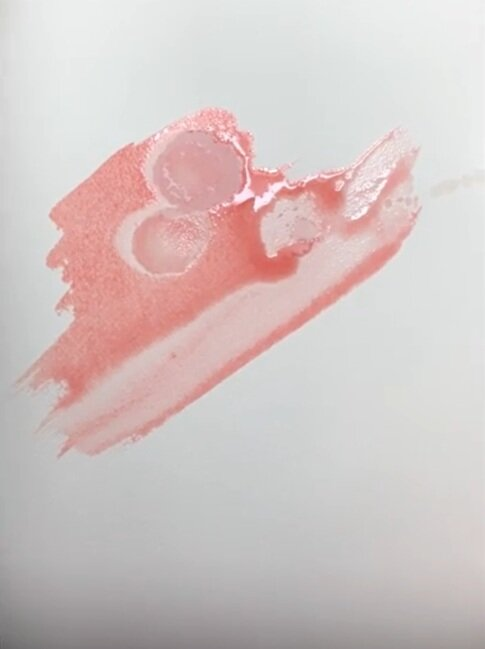 Dropping rubbing alcohol onto pigment creates circular patterns.