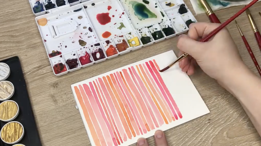 Skillshare instructor Caitlin Sheffer demonstrates making watercolor lines on a piece of paper—a beautiful example of creative self care.