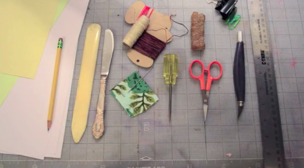Some of the essential tools for a simple book binding, including a needle and thread, bone folder, and book awl.