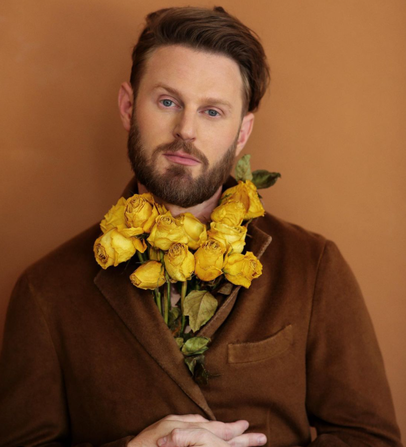 Image via Instagram   @bobby    Bobby Berk poses with a bouquet of yellow roses.