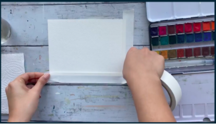 Skillshare instructor Alifya Tarwala secures her watercolor paper before beginning her landscape painting.