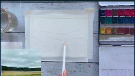 This watercolor illustration will be an outdoor landscape scene. Here, the artist sketches out the general shape of the trees, mountains, and pond she will be painting.