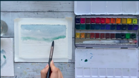The artist uses a medium-sized brush to lay down the first layer of watercolor paint, starting with lighter colors.