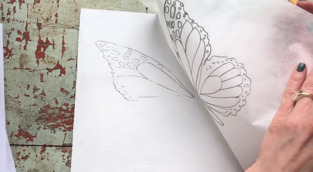 Transfer the first side of the butterfly onto a clean surface by placing the tracing paper face down and tracing again.