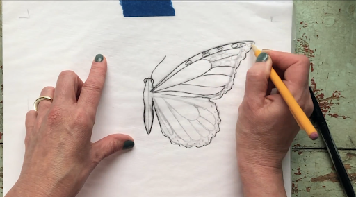 Trace your butterfly half using a dark graphite pencil and a sheet of tracing paper.