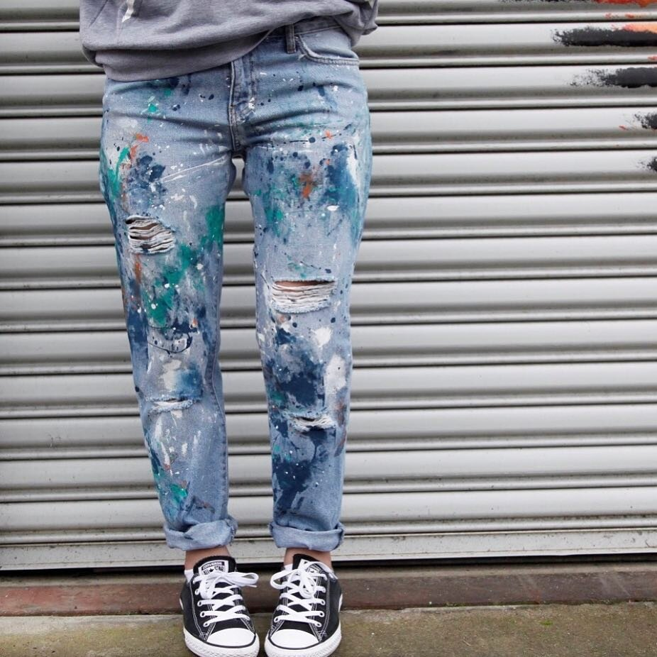 A colorful pair of paint splatter jeans by Painted Peacock Creations, LLC