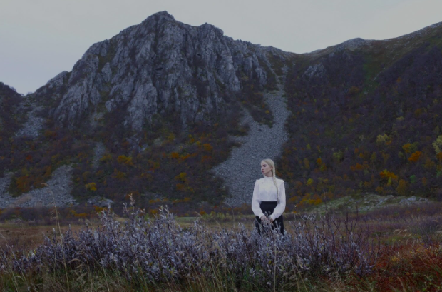 This artist self portrait by Mariell Améli features her standing in a natural landscape, surrounded by flowers. |  Image © Mariell Améli