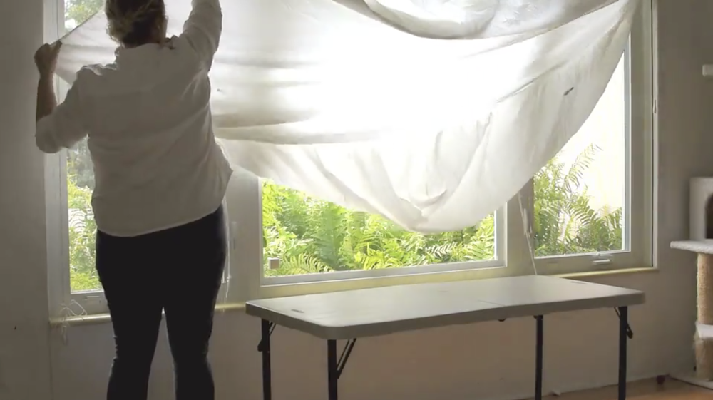 Skillshare instructor Kristina Turner shows how she transitions her own living room into a studio space, using a sheet to diffuse the natural light.