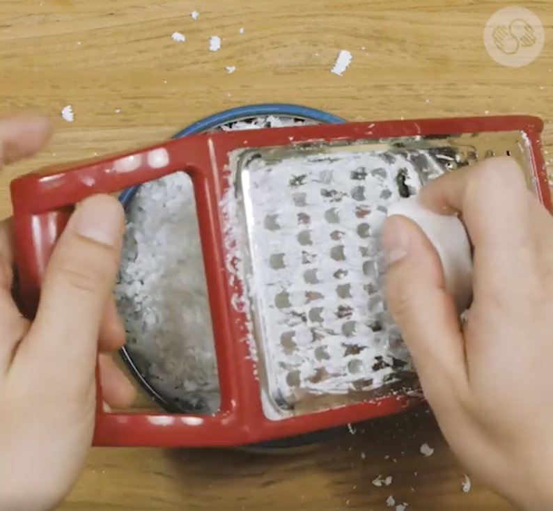 Take your soap bar and grate it into a bowl.