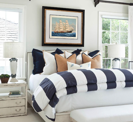 Coastal bedroom with nautical bedding and artwork.