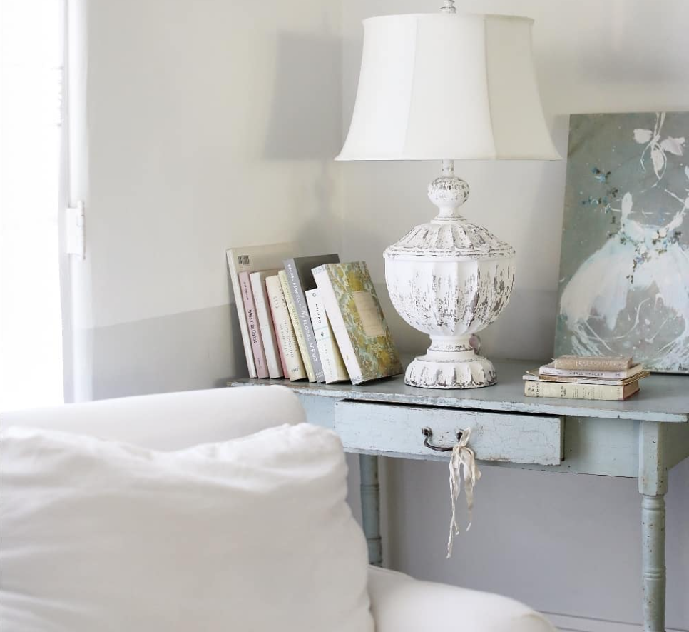 Vintage design elements in a room, including distressed furniture and antique books.