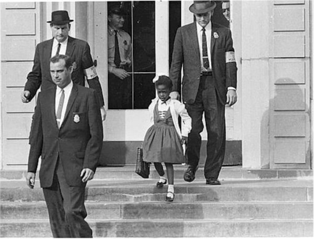 William Frantz Elementary School, New Orleans, 1960. After a federal court ordered the desegregation of schools in the South, U.S. Marshals escorted Ruby Bridges to and from school amidst protestors.    (1)