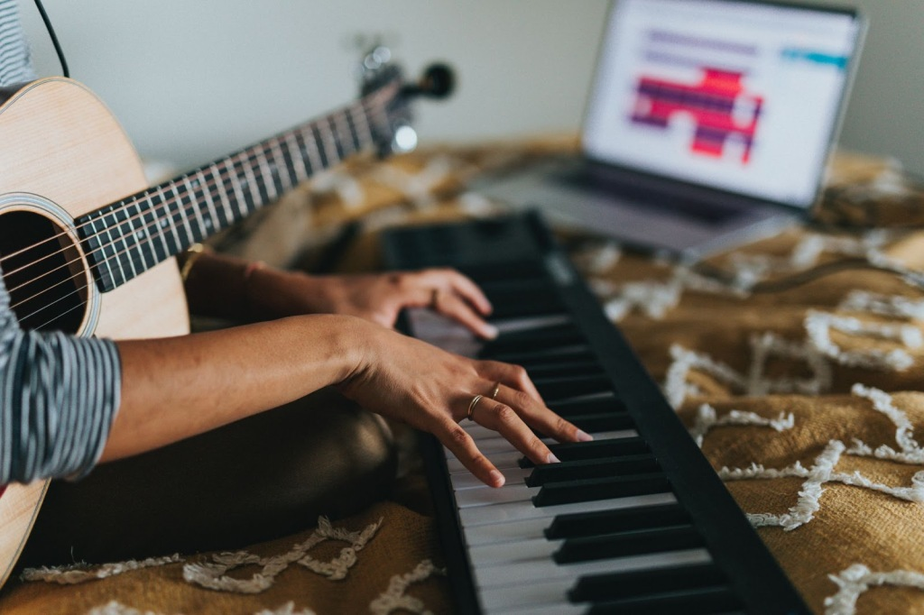 person with guitar and piano